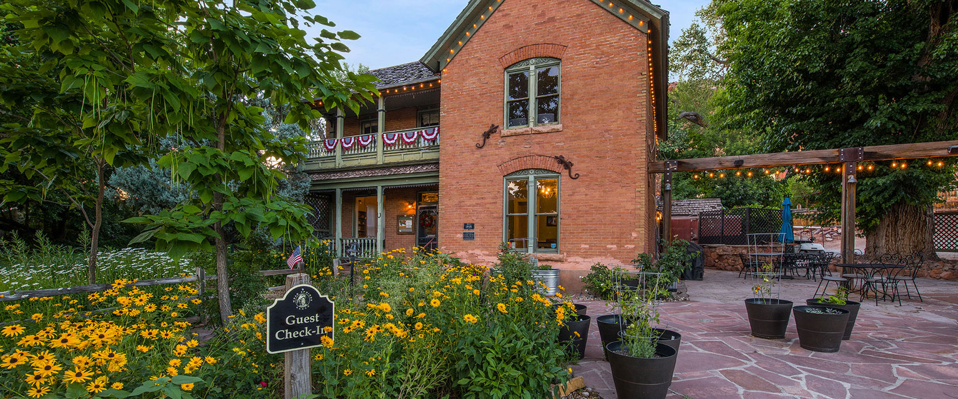 The pool area at Moab Springs Ranch is furnished with white chaise lounges and side tables and is enclosed by a steel rod fence, tall trees and the natural barrier of a sandstone cliff.