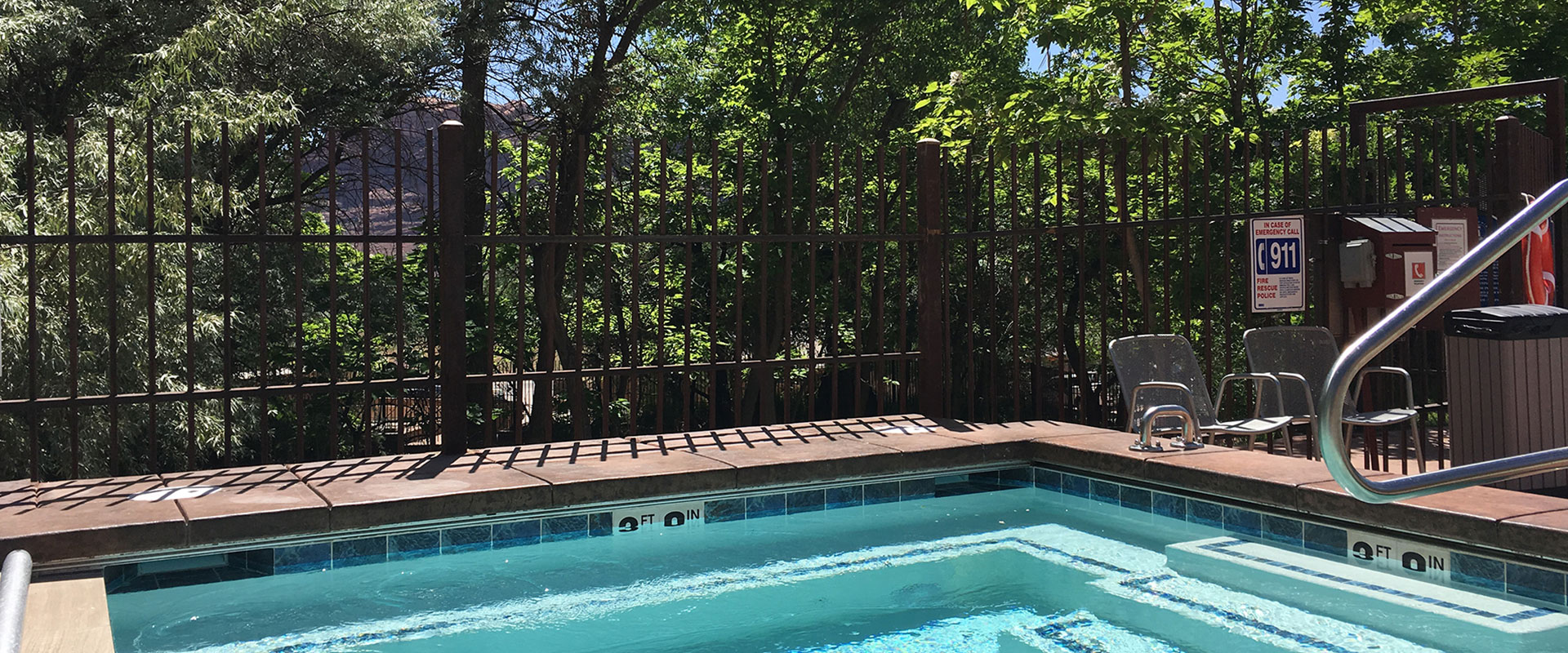 A man-made pond with paved coral pink brick, flows into a natural stream running through the green private parkspace of Moab Springs Ranch.