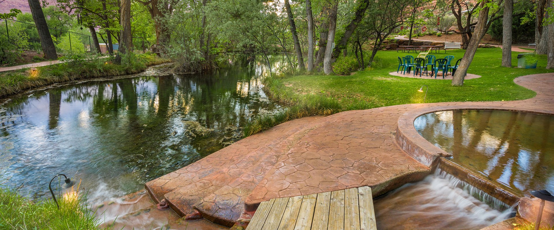 Two males on bicycles are riding on a bike path alongside the lush greenery of trees and vegetation, large red brown boulders and the large rectangular Moab Springs Ranch sign.