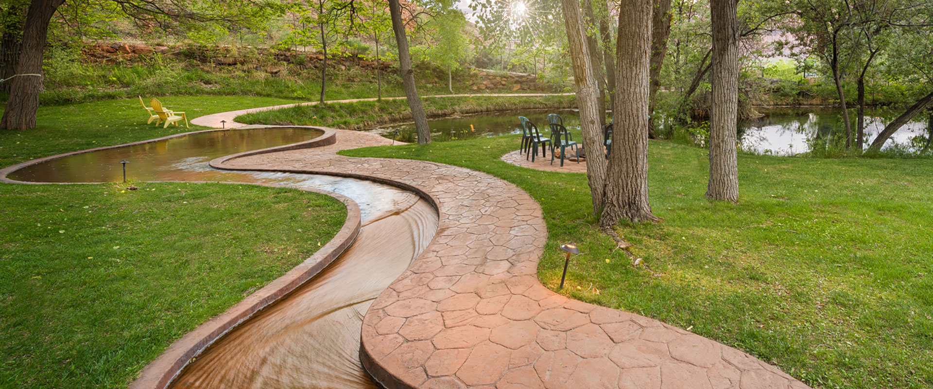 Two female guests sitting on plastic patio chairs and an older male holding a beer are warming themselves by a pitfire at Moab Springs Ranch.