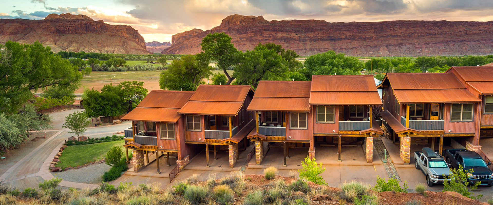 The Moab Springs Ranch sign faces oppposite an empty road, a view of the vast grasslands and towering sandstone mountain cliffs of Moab, Utah.