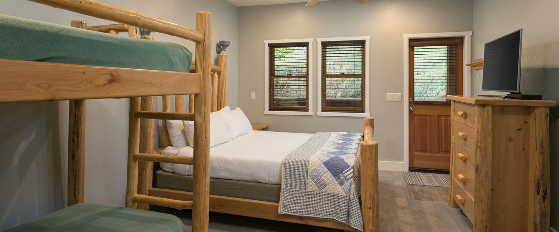 The sandstone cliffs are covered with a dusting of snow in the winter in Moab, Utah, with black skeletal branches of trees in the foreground.
