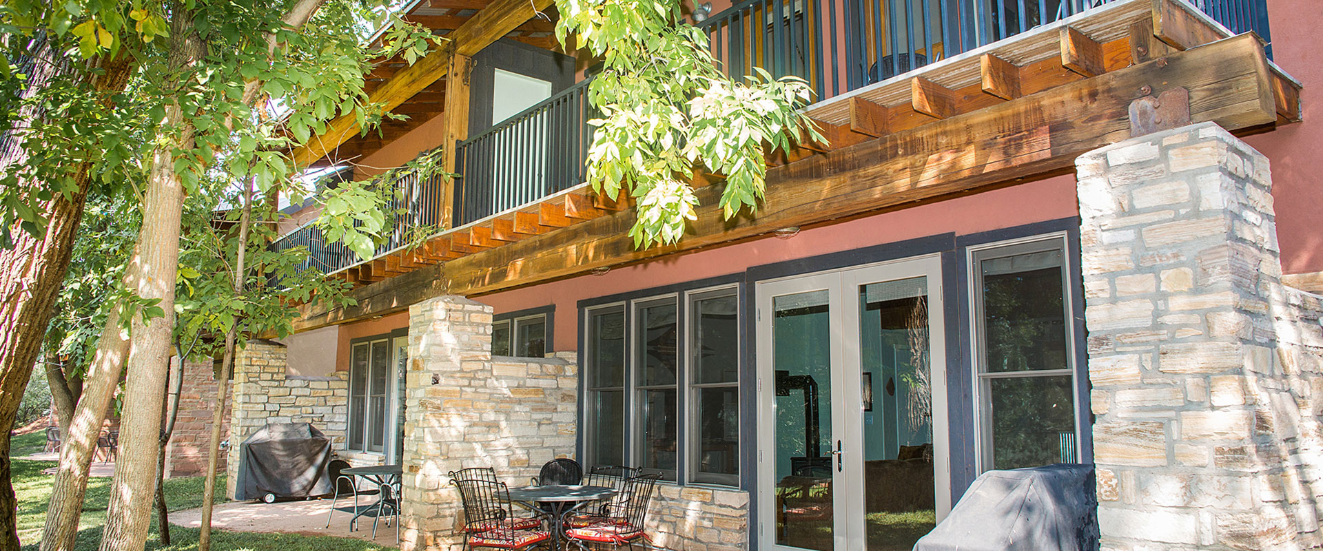 The evening sunset is obscured behind the imposing black unilluminated sandstone cliffs of Moab, Utah.