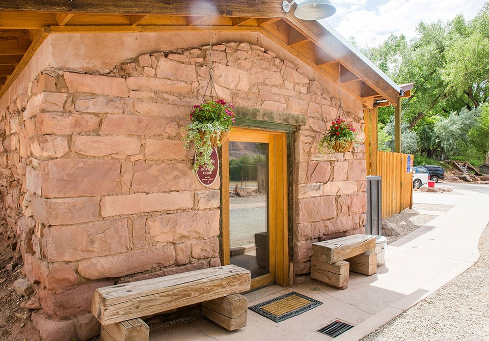 A historically preserved ranch house at Moab Springs Ranch featuring beige brick construction, a wood roof, log seating and a woodframed-glass door entrance.