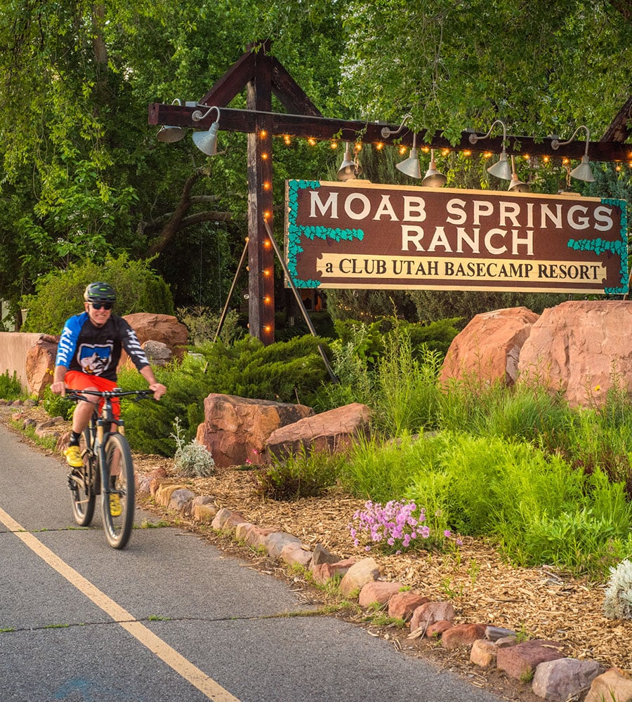A smiling male bicyclist, wearing a helmet and dark sunglasses, rides along the bike path passing the Moab Springs Ranch sign, large boulders, cobble rocks and green flora and fauna.