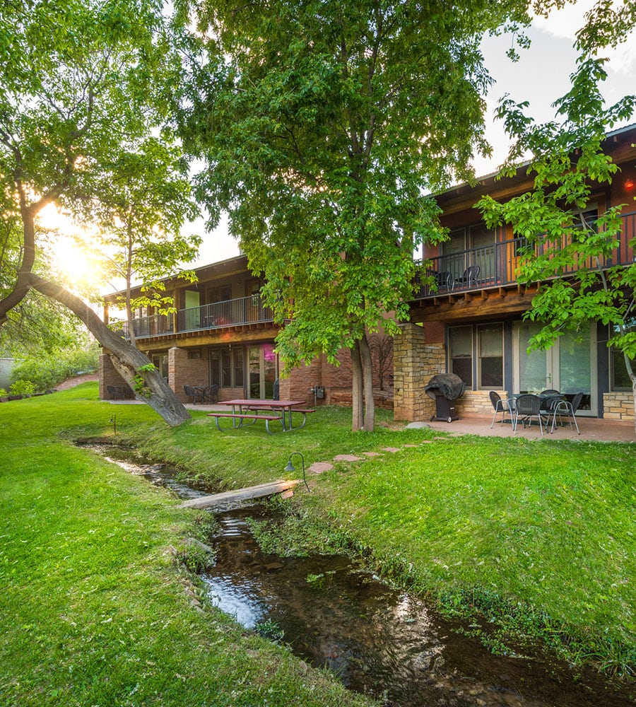 Two units of brick and wood townhouses stand side by side with tall green cottonwood trees and a stream in the front the properties at Moab Springs Ranch.
