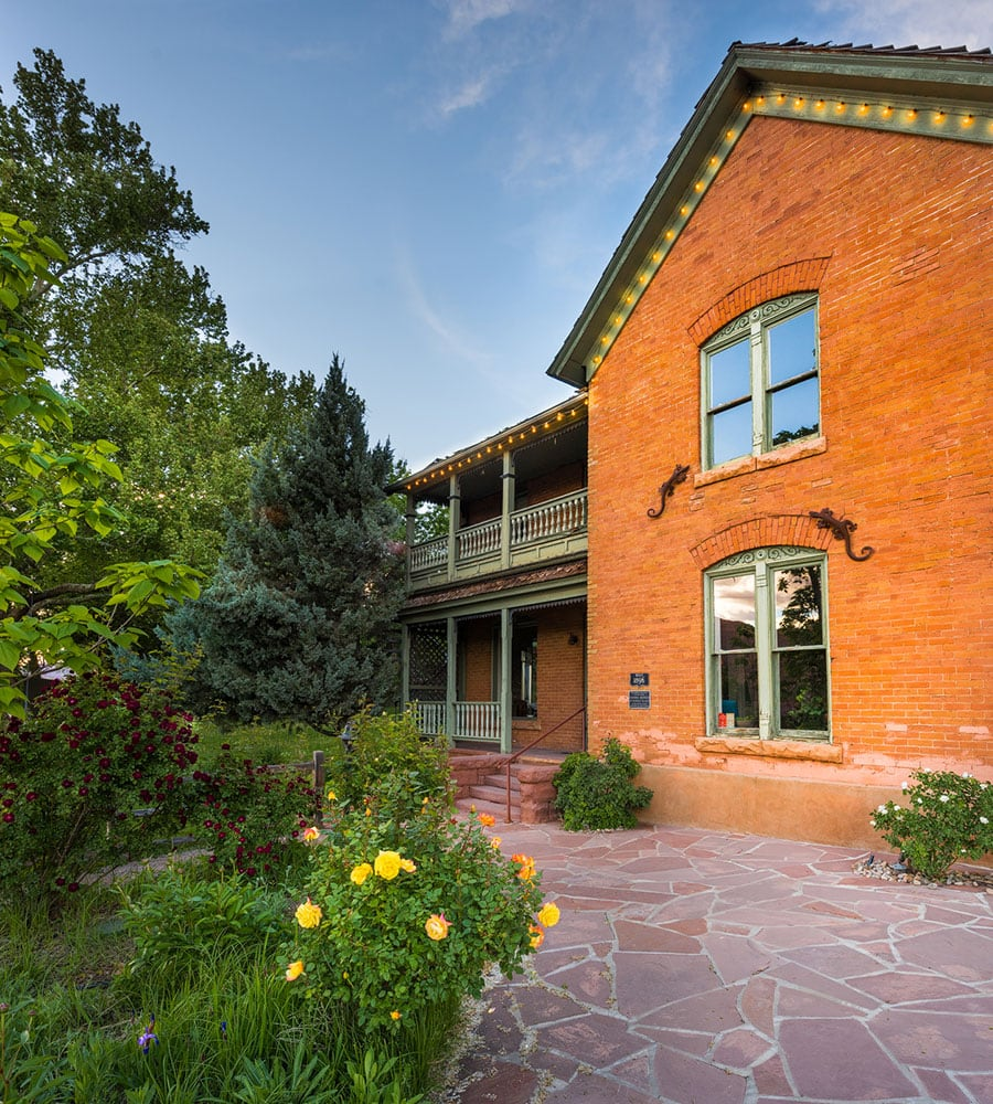 The Main House at Moab Springs Ranch is a two story brown brick structure that sits amongst lush tall trees with multi-colored vegetation at its' doorstep.