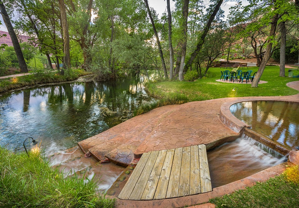 A shallow pond area, paved with beige stone is surrounded by grass, cottonwood trees and lounge chairs at Moab Springs Ranch.