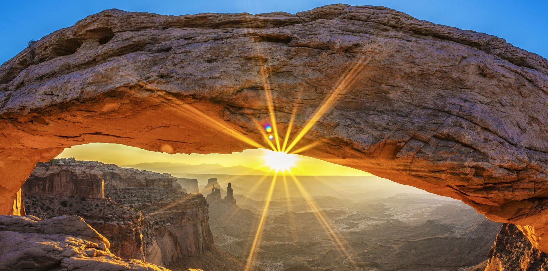 A large panoramic view of the underside of a large sandstone arch with the rays of the sun shining through at Arches National Park in Moab, Utah.