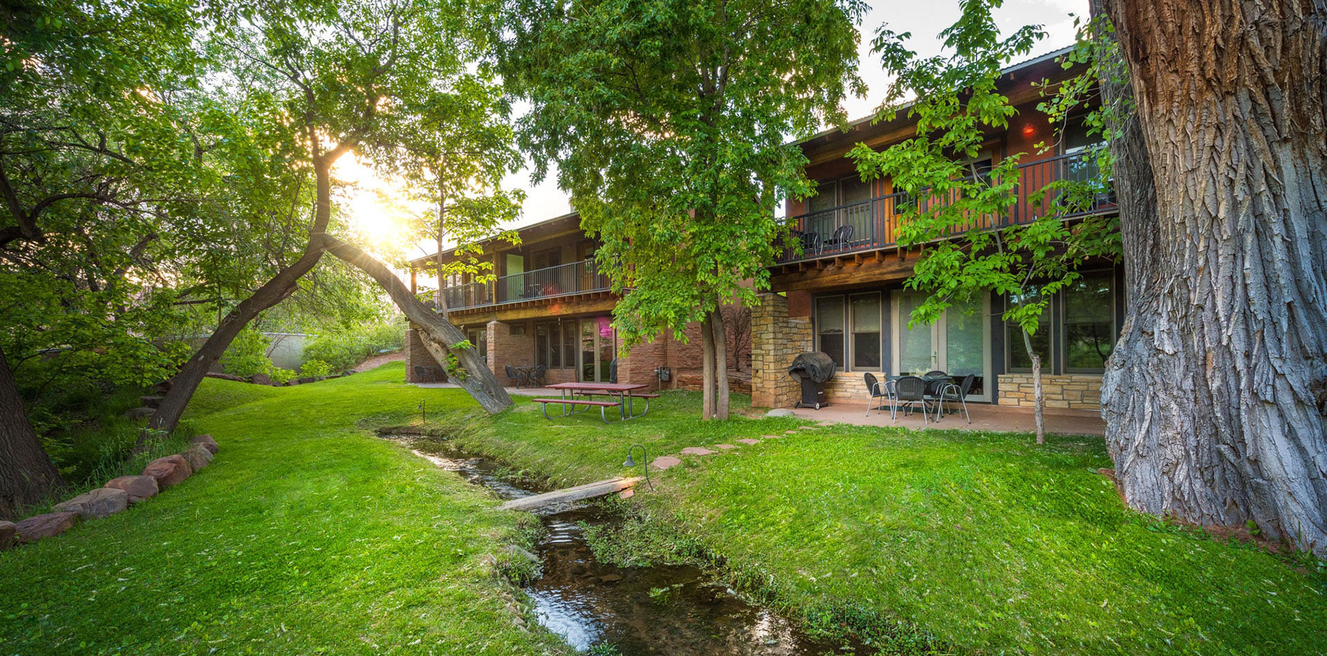 Panoramic view of two townhouse units at Moab Springs Ranch facing vibrant green lawns, cottonwood trees and a shallow stream.