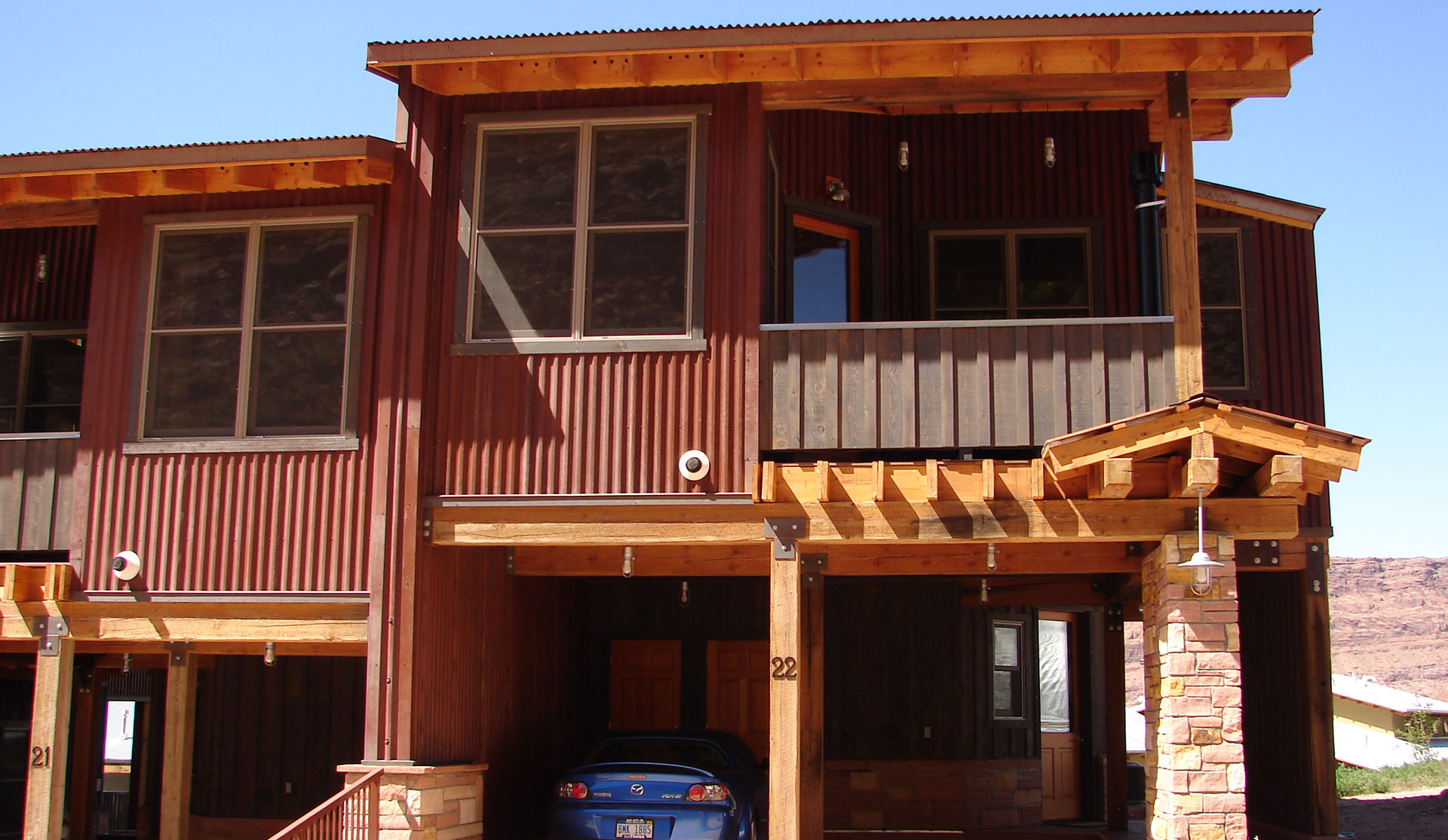 Front of view of townhouse entryways to Units #21 and #22 at Moab Springs Ranch, featuring two-car garages, covered decks and large woodframed windows.