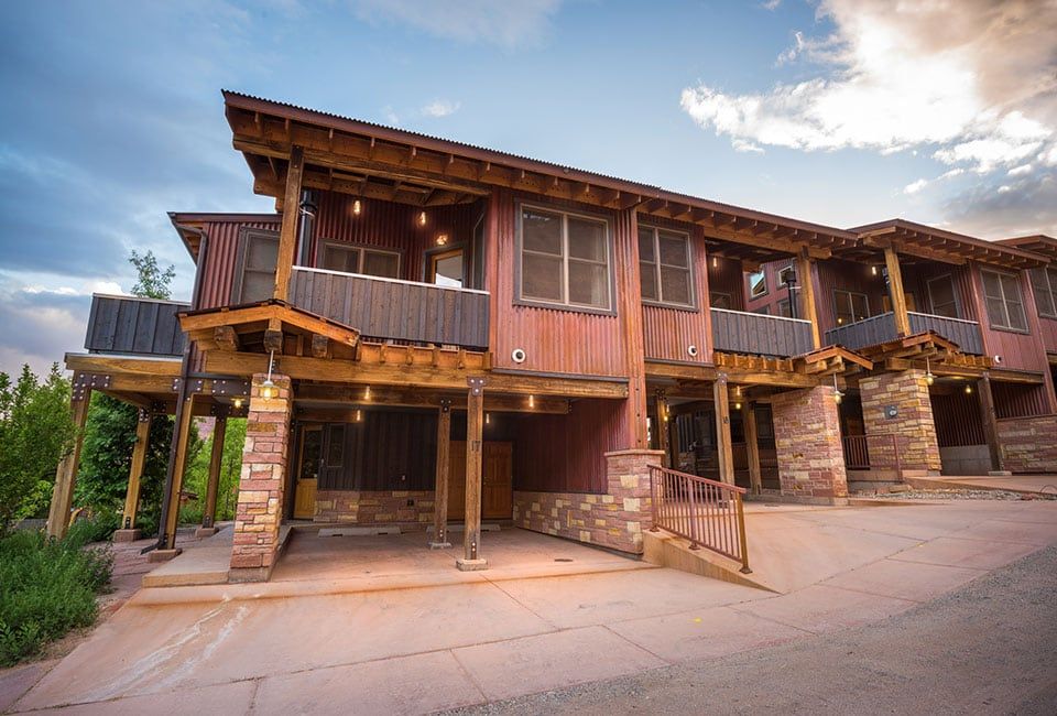 A row of townhouse units at Moab Springs Ranch features two-car garages built with brick and wood columns, covered balconies and large square woodframed windows.